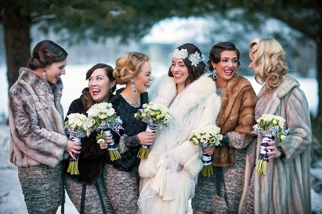 A bridal party wearing fur stoles in the snow