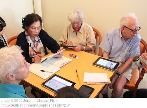 Seniors sitting at a table using iPads