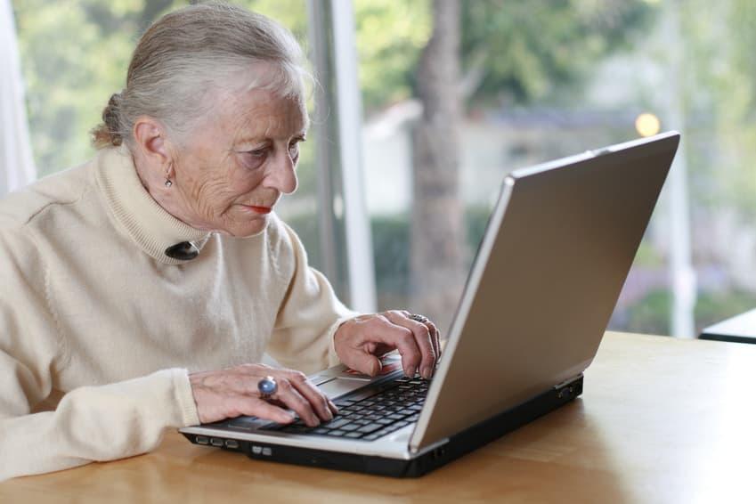 Elderly lady typing on laptop.