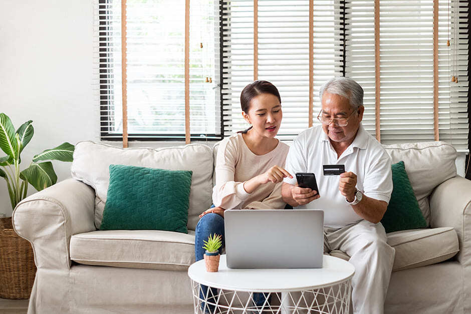 young woman helping senior use a phone on the couch