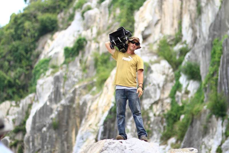 Filmmaker standing on a rock filming on location