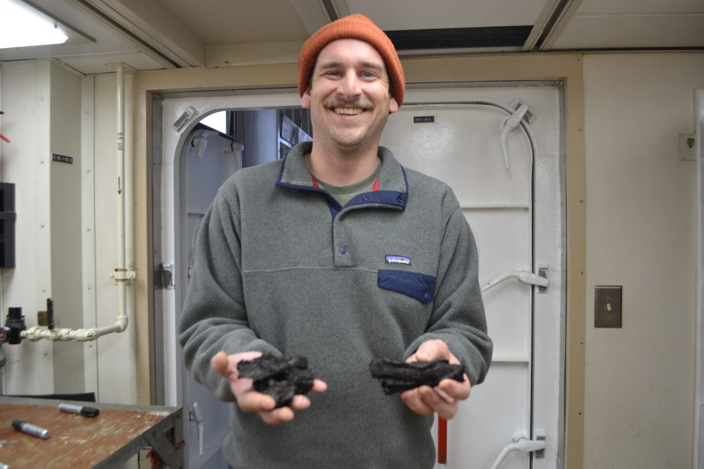 Evan Davis with a specimen obtained from Axial Caldera, Credit: University of Washington, V18