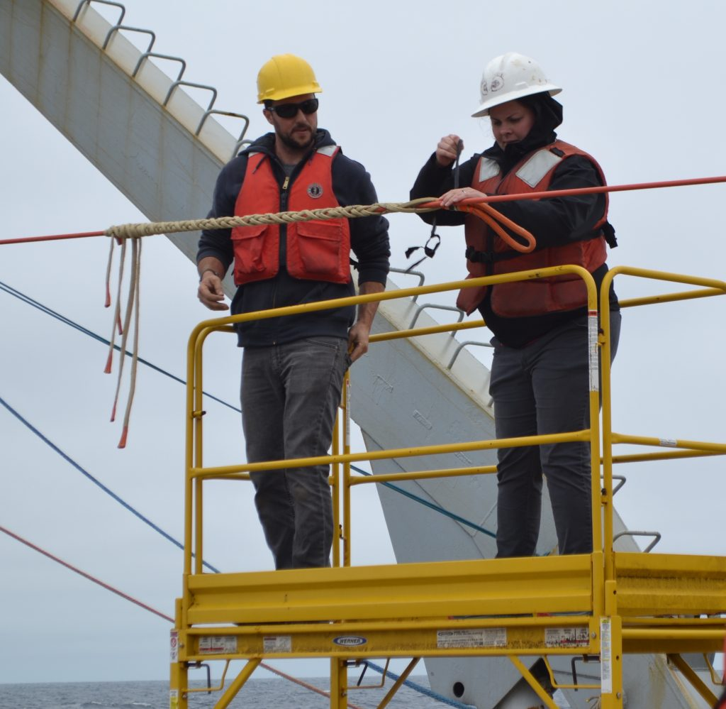 Grays Harbor College recent graduate Jasmine Durant assists APL Engineer Nic Hart with yale grips while deploying the deep profiler at Axial Base. Credit: R. Centurion, Univesrity of Washington,V18