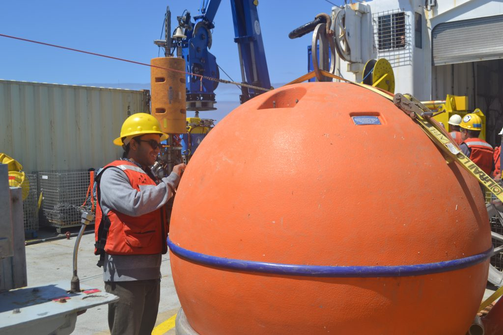 Recent University of Washington graduate Yash Meghare inspects the animals that had made the recovered top float of the Oregon Offshore Deep Profiler Mooring their home. Credit: K. Gonzalez, University of Washington, V18.
