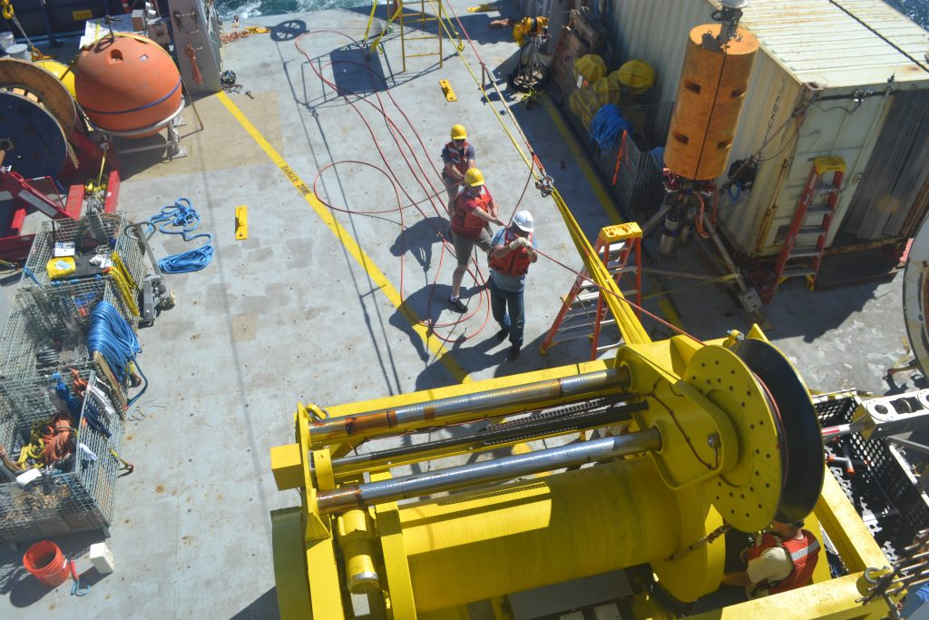 APL Engineers Mike Kenny, Chris Siani, and Chris Harding keep tension on the Deep Profiler cable at the Oregon Offshore site while it is wound on the winch during recovery. Credit: Y. Meghare, University of Washington, V18.
