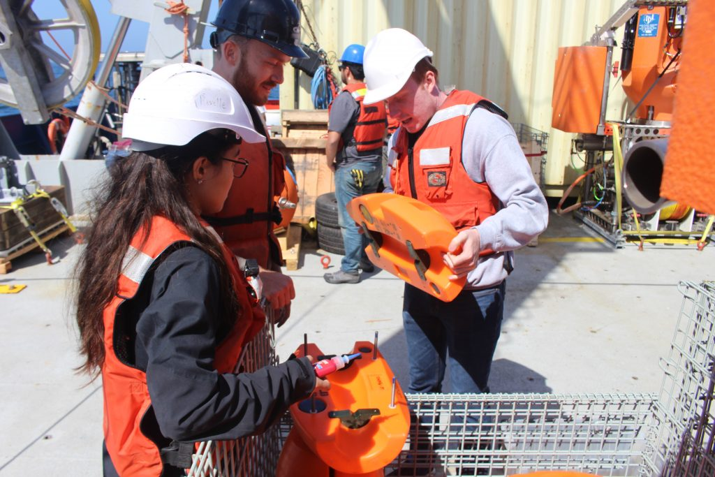 University of Washington undergradautes Ashley Lobao (left), Leland Wood (right), and Queens College undergraduate Emilio Tensin (middle) prep football floats to be deployed on the Shallow Profiler Mooring legs at Oregon Offshore. Credit: S. Nelson, University of Washington, V18.