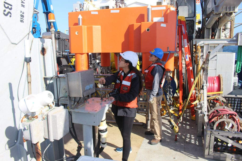 University of Washington undergraduate Ashley Lobao runs the A-Frame on the Roger Revelle while APL engineer Dana Manalang supervises. In the background is the 200 m platform before being deployed at the Oregon Offshore Site. Credit: Spencer Nelson, University of Washington, V18.