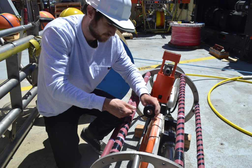 Spencer Nelson secures hosing to the EOM cage on deck. Credit: University of Washington, V18.