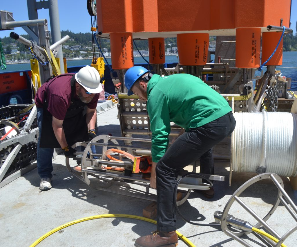 Queens College undergrad Emilio Tesin helps APL Engineer Mark Harding move the EOM cage during prep in Newport. Image Credit: Mitch Elend, University of Washington, V18.