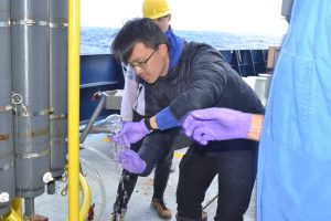Bing Yu Lee, University of Washington ESS undergratuate student, learns to take fluid samples collected with the CTD Niskin bottles. Credit: M. Elend, University of Washington, V18.