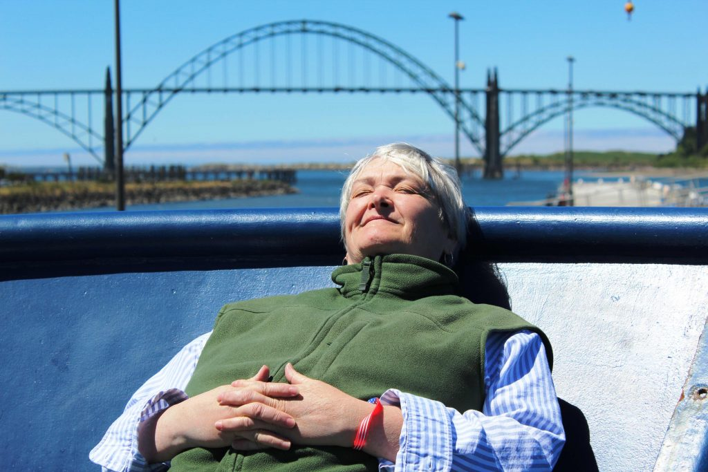 Deb Kelley, Chief Scientist of the Cabled Array cruises, catches a brief bit of downtime in the sun onboard the R/V Revelle during the Legs 1-2 transition. Credit. T. Manning, University of Washington, V18.