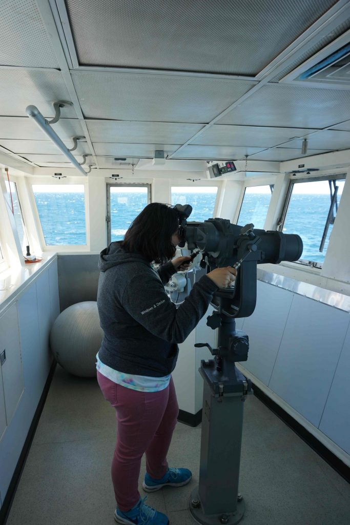 "Katie Gonzalez uses the high power ""binoculars"" on the bridge of the Revelle during the student tour. Credit. B.-Y. Lee, University of Washington, V18."