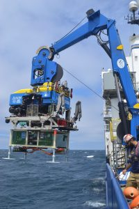 Jason launched over the side of the R/V Revelle during the NSF-funded OOI Cabled Array expedition. A low voltage junction box, built by the UW Applied Physics Lab, is latched under the vehicles 'belly' to safely take it to the seafloor. Credit: M. Elend, University of Washington, V18.