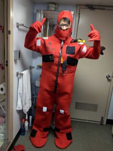Bing practices putting on a survival suit prior to sailing on the VISIONS18 cruise.