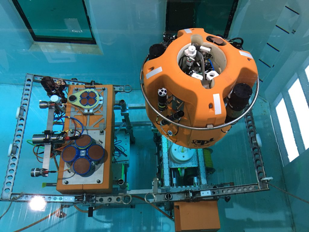 A Shallow Profiler winched science pod and stationary platform, which host 18 instruments (e.g. pH, CO2, temperature, chlorophyll, zooplankton, nutrients, currents) undergoes testing in the School of Oceanography saltwater tank. The platforms will be deployed 600 ft beneath the oceans surface. Since 2015, three of these pods have made >27,000 profiles, providing unprecedented measurements of our dynamic ocean in real-time. Credit: D. Kelley, University of Washington.