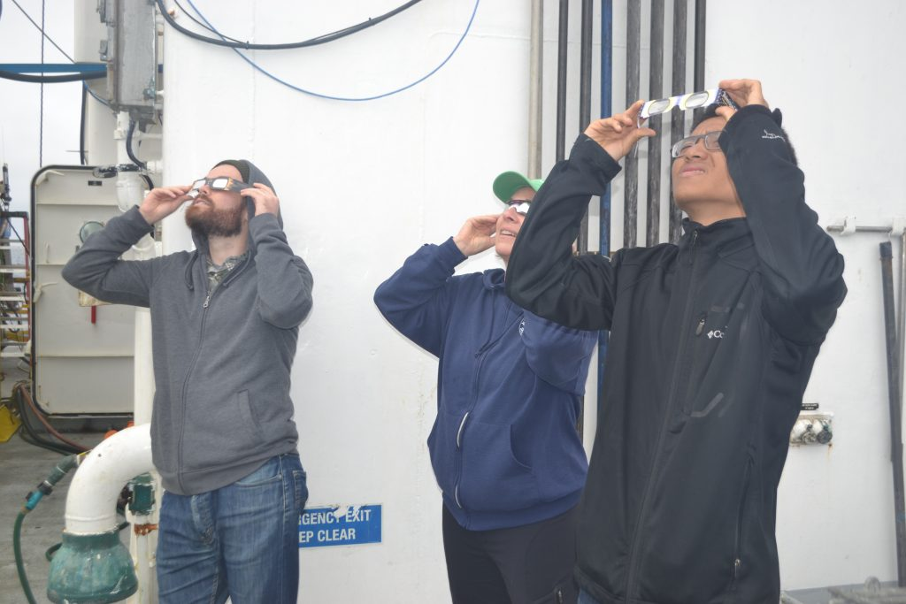 Scientists and students onboard the R/V Revelle try to catch a glimpse of the solar eclipse under cloudy skies during the transit to Axial Caldera. Credit: M. Elend, University of Washington, V17.
