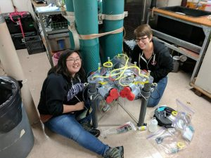 UW Graduate Student Theresa Whorley (right) and undergraduate Michelle Lee (left) prepare a Moquito flow meter that allows calculation of fluid flux into and out of the sediments at Southern Hydrate Ridge - a tough measurement to make. Credit: Kevin Eyer, Kingston Middle School, V17.