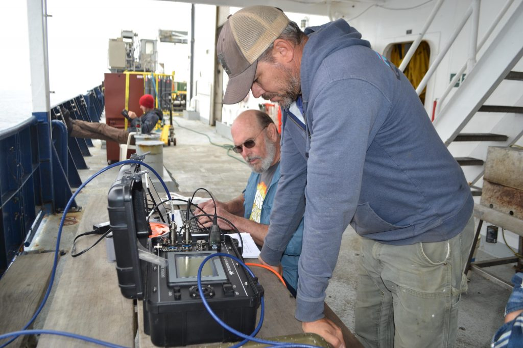 University of Washington, Applied Physics Laboratory engineers Skip Denny and James Tilley acoustically retrieve oxygen and temperature data from a seafloor instrument built by Clare Reimers at Oregon State University. Credit: M. Elend, University of Washington, V17.