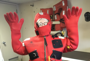 Cheryl Greengrove successfully puts on a survival suit as part of the safety training on the R/V Revelle. Credit: H. Zulaikha, University of Washington, V17.