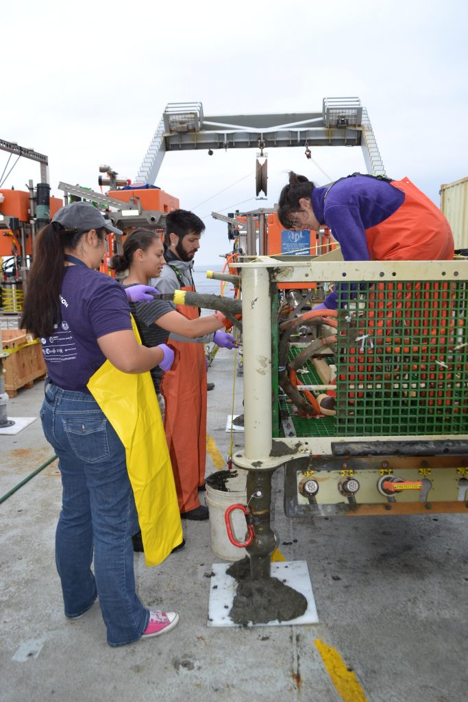 Katie Gonzalez, Eve Hudson, Alex Andronikides, and Kelsy Cain (in junction box) help clean the LV01C junction box that had been tipped on its side (still fully operational, however) for a few years at the Oregon Offshore Site. Credit: M. Elend, University of Washington, V17.