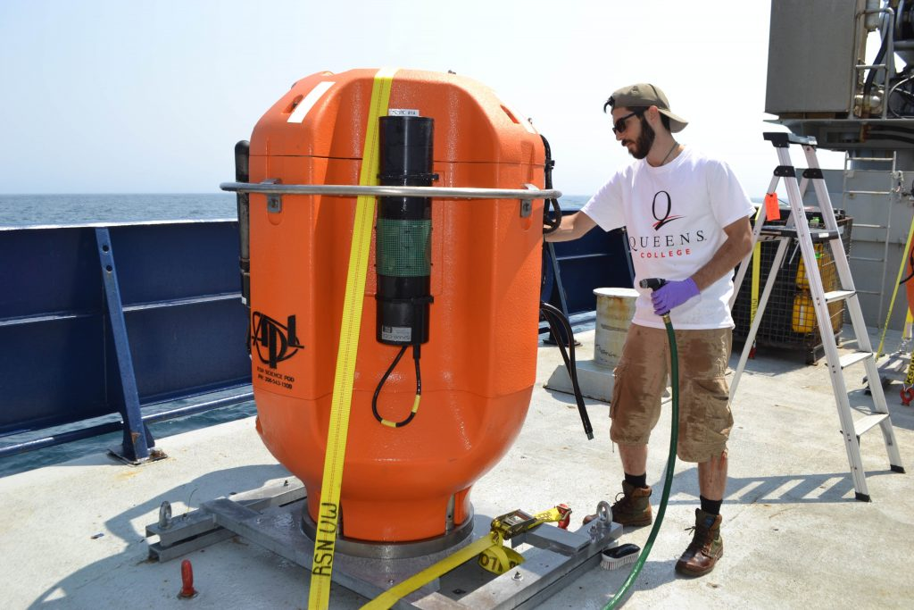 Alex Andronikides from Queens College, New York helps clean a Shallow Profiler Mooring science pod that was installed off the Oregon coast in 2016. Credit: M. Elend, University of Washington, V17.