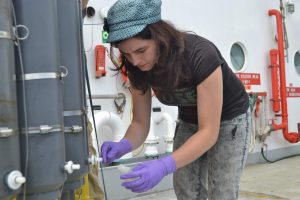 Monique Bell samples fluids from 200 m beneath the oceans' surface collected with a CTD during the UW-NSF-OOI Cabled Array operations and maintenance cruise. Credit: M. Elend, University of Washington.