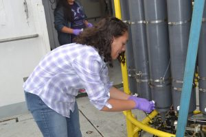 Eve Hudson, a high school student taking classes at Peninsula College, learns to sample fluids collected with the CTD on the first cast of the Cabled Array OOI-NSF-UW VISIONS'17 cruise. Credit: M. Elend, University of Washington.