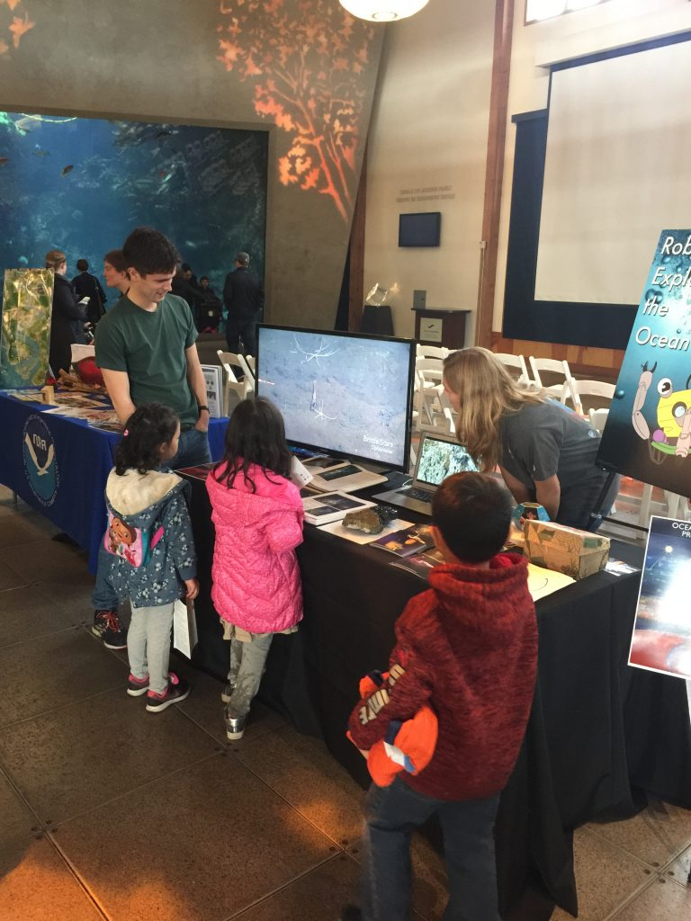 Young explorers at the Seattle Aquarium's Discover Science event view brittle stars imaged at depths of 2900 m during a Cabled Array cruise. Dana Manalang and Brendan Philip, part of the UW Cabled Array team share the excitement of exploring and instrumenting the deep.