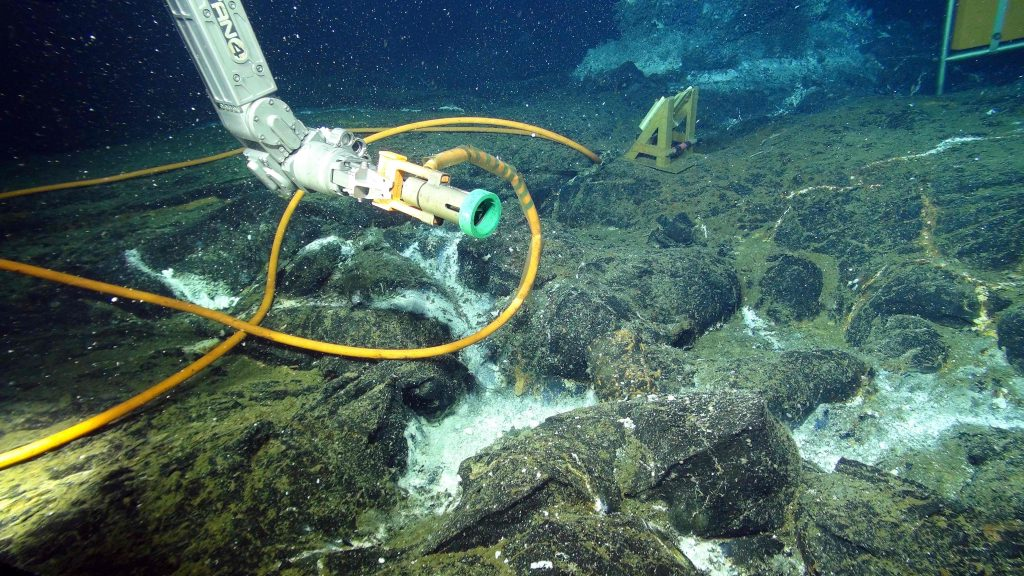 """The ROV Jason """"looks"""" at a hybrid underwater wet-mate connector that connects the high definition camera to a ~ 4 km long extension cabled attached to Primary Node PN3B at the summit of Axial Seamount. This connection provides a 10 Gbs communication path to the terrestrial Internet located >300 miles to the east. White bacterial mats line fractures in the lava-covered seafloor where diffusely flowing fluids are exiting the seafloor. Credit: UW/NSF-OOI/WHOI; V16."""