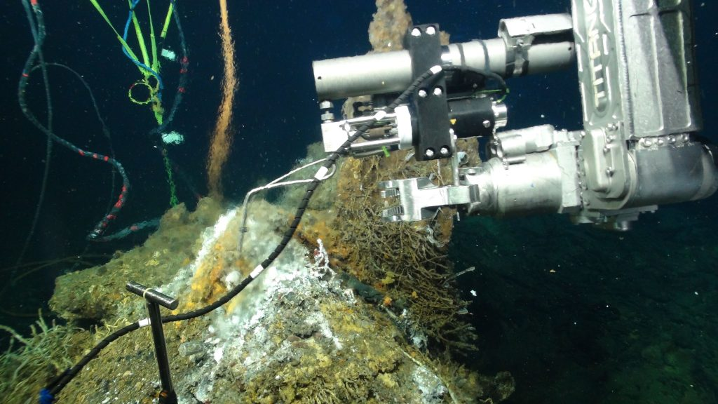 A titanium isobaric gas-tight sampler (IGT) is used to sample fluids with dissovled gases in a high temperature vent on the El Gordo metal sulfide chimney located in the International District Hydrothermal Field at ~ 1500 m water depth on Axial Seamount. The base of the cabled RAS fluid sampler and microbial DNA sampler mooring is in the background. Credit: UW/NSF-OOI/WHOI; V16