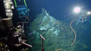 """The cabled digital still camera streams images of Jason (Dive J2-932) live back to shore in real time as the vehicle works at the active hydrothermal vent called 'El Gordo' in the International District Hydrothermal Field - depth is 1500 m, and >300 miles offshore. The hydrothermal fluid sampler, called the RAS, is shown to the left, which allows fluid samples and temperature to be taken for a year. The instrument can be run in """"mission mode"""" where samples are preprogrammed, or in """"sponse mode"""" where missions are interrupted by operators to take samples - such as was done during the eruption of Axial Seamount in 2015. Credit: UW/OOI-NSF/WHOI, V16."""