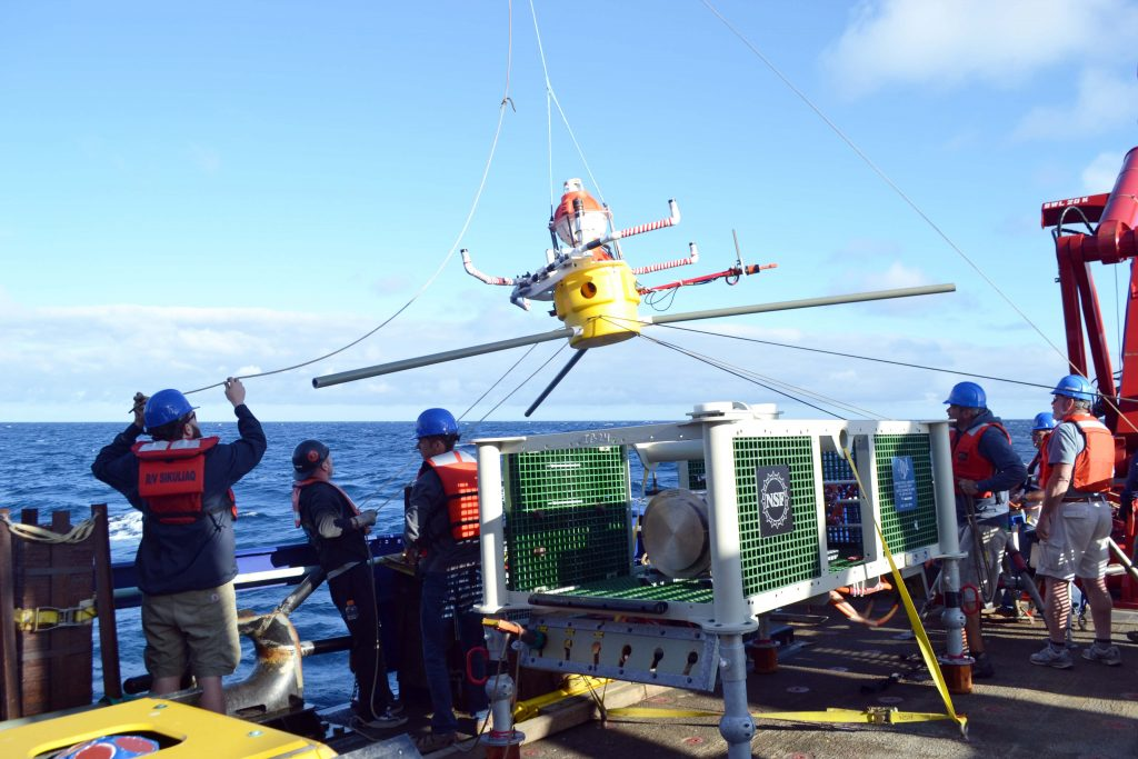 An HPIES instrument is being installed off the starboard side of the R/V Sikuliaq ~ 125 km offshore Newport Oregon near the base of the Subduction Zone. This instrument utilizes a bottom pressure sensor, an inverted echosounder and a horizontal electrometer to provide insights into the vertical structure of current fields, near-bottom water currents, and water properties including temperature, salinity, and specific volume anomalies. It was built at the Applied Physics Laboratory. Credit: M. Elend, University of Washington, V16.