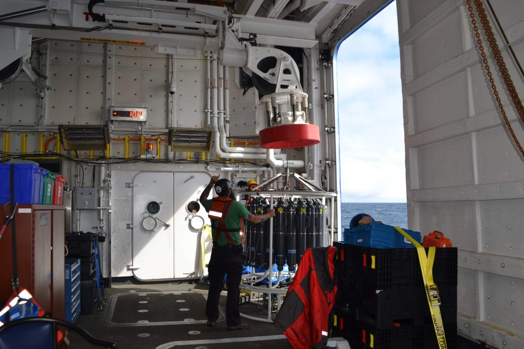 A CTD rosette being deplyed from the Baltic room on the R/V Sikuliaq during the VISIONS'16 expedition. Analyses of water samples from the Niskin bottles are used to verify instruments on the Cabled Array. Credit: M. Elend, University of Washington, V16.