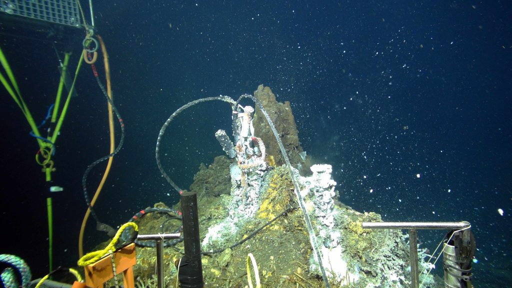 A Hydrothermal Vent Cap at the top of the actively venting chimney called 'El Gordo', traps high temperature hydrothermal fluid. An intake nozzle from the mass spectrometer allows measurement of gas chemistry in real-time, sending data at the speed of light back to shore. Another nozzle sucks in vent fluids for sampling and for filtering of microbial DNA: the samples fluids and DNA are recovered during annual Cabled Array maintenance cruises for follow-on shore-based analyses. Credit: UW/NSF-OOI/WHOI; Dive J2-912, V16.