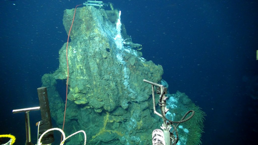 A temperature-resistivity sensor, with its wand now embedded in a sulfate-rich chimney (white, right) sends real-time data to shore from the Escargot chimney, 5000 ft beneath the oceans' surface and >300 miles offshore. Resistivity is an analogue for fluid chlorinity. Numerous hydrothermal vents in the International District Hydrothermal Field at the summit of Axial Seamount are boiling. Credit. UW/OOI-NSF/WHOI; Dive J2-912, V16.