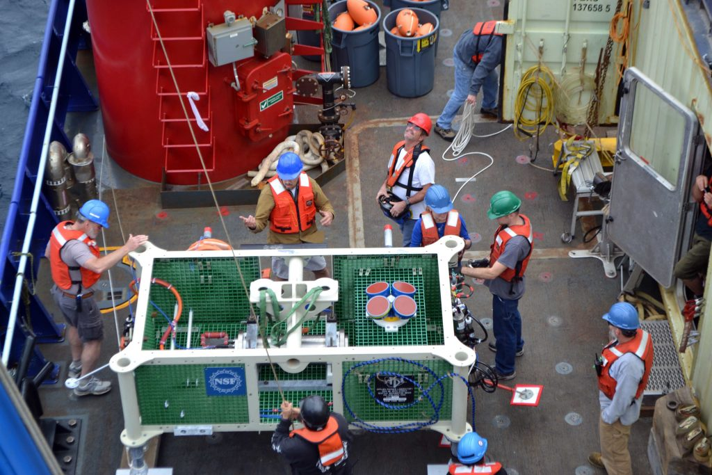 The engineeing team from the Applied Physics Laboratory at the UW and the crew of the R/V Sikuliaq prepare the low-power junction box for installation at the Slope Base site near the Cascadia Margin, 9500 ft beneath the oceans' surface. Credit. M. Elend, University of Washington, V16.