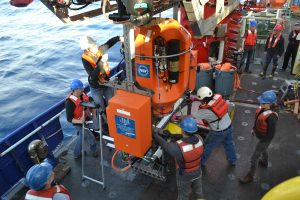 Final preparations on the whiched, instrumented Science Pod before it is latched under the belly of the ROV Jason for installation on the Shallow Profiler Mooring at Axial Base. Credit: M. Elend, University of Washington, V16.