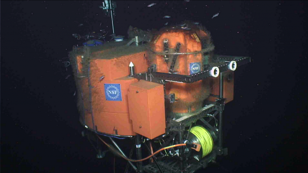 The ROV Jason surveys the Shallow Profiler platform located ~ 600 ft beneath the oceans' surface. Eighteen instruments on the platform and profiling science pod have been sending data live to shore for a year, all connected to the Internet. Both science pods have now been replaced during the annual, planned maintenance of this system. Operation of this infrastructure takes place at the University of Washington Operations Center in the School of Oceanography. Credit: UW/OOI-NSF/WHOI; V16.