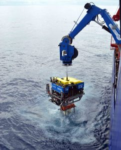 The ROV Jason breaches the oceans surface latched into an instrumented Platform Interface Assembly that has been installed for a year on a Shallow Profiler Mooring at the base of Axial Seamount. Connected to the submarine cable, the instruments have been sending sending data live back to shore since summer 2015 from 600 ft beneath the oceans' surface. Credit: M. Elend, University of Washington, V16.
