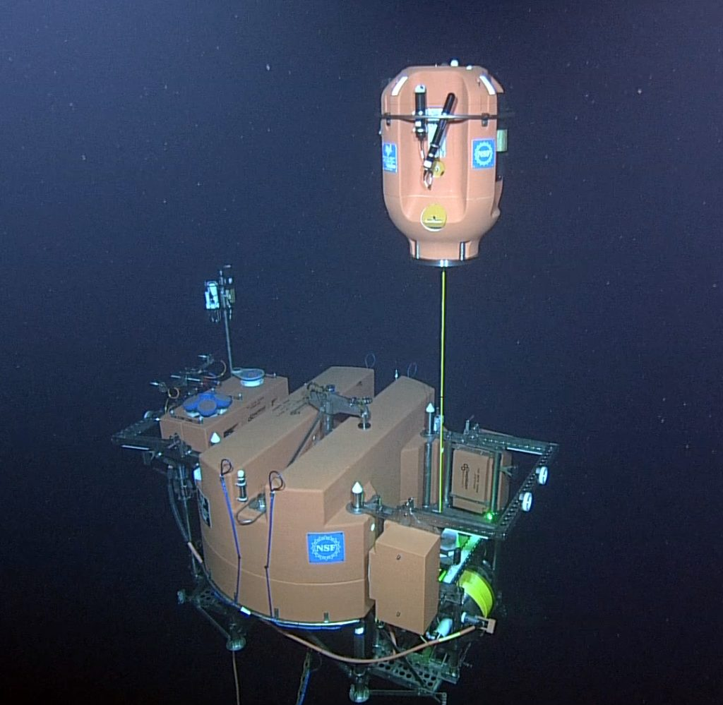 Since the late summer, 2015, each of the three cabled Shallow Profiler Mooring winched science pods have made >7000 cycles from 600 ft water depth to just beneath the oceans' surface. Real-time command and control of these systems through the Internet provides response capabilites such that the science pods can be stopped to take key measurements in response to events that include the passing over of biologically-rich thin layers. Credit: University of Washington, NSF-OOI/ROPOS, V15.