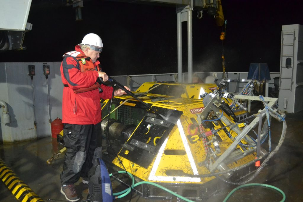 Kent Fletcher (OSU) uses a power washer to clean external surface of a trawl-resistant Benthic Experiment Package recovered from the EA Shelf (60 m) Site. Credit, Mitch Elend, UW; V15.