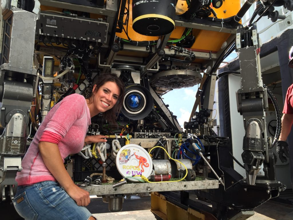 Tracie posing with her artfully decorated marker that ROPOS will emplace on the seabed at Axial Seamount. Credit: Vinnie (ROPOS); V15.