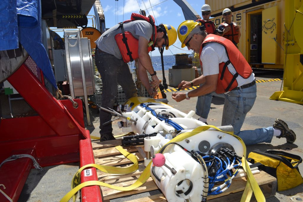 Tim McGinnis and Nick Michel-Hart of the UW Applied Physics Laboratory begin to disassemble and inspect the crawler recovered from the Deep Profiler Mooring at Axial Base. Credit: Mitch Elend, UW; V15.