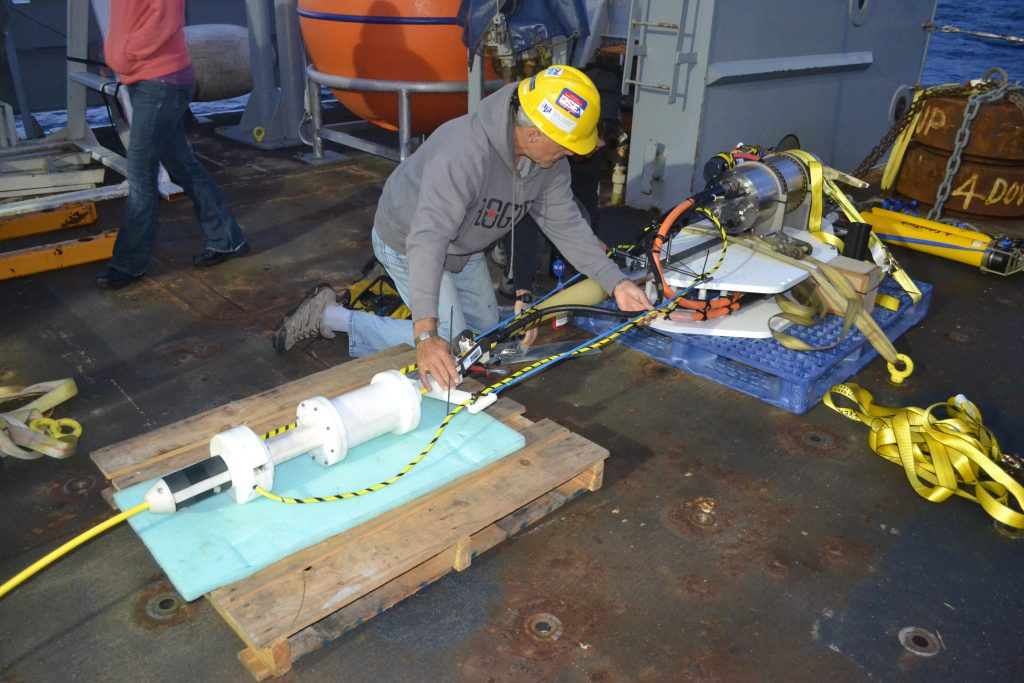 Tim McGinnis from the UW Applied Physics Laboratory prepares the docking station for the Slope Base Deep Profiler that was installed during Leg 2 of the NSF-OOI-UW Cabled Array VISIONS'15 cruise. Credit: Mitch Elend, University of Washington, V15.