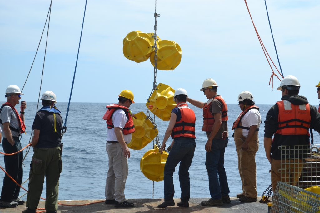 "Yellow ""hard hats"" encase glass floatation spheres that top the infrastructure on the Deep Profiler Morrings. These spheres were being installed from the fantail of the R/V Thompson as part of the Slope Base Mooring during Leg 2 of the NSF-OOI-UW Cabled Array VISIONS'15 crusie. Credit: Mitch Elend, University of Washington. V15."