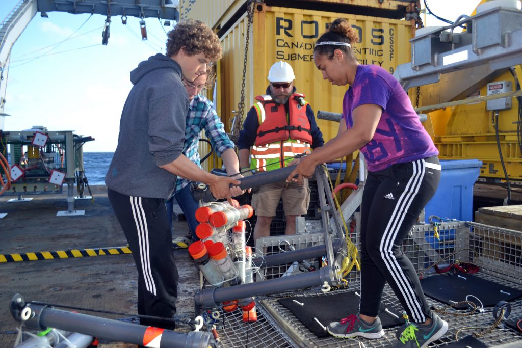 "UW undergraduate students Jesse, Lauren, and Kearstin help move a ""mosquito"" off of ROPOS's tool sled during Leg 1. This instrument has been measuring the flow of fluids into and out of a methane seep site at Southern Hydrate Ridge since it was installed last year. Credit: Mitch Elend, University of Washington."