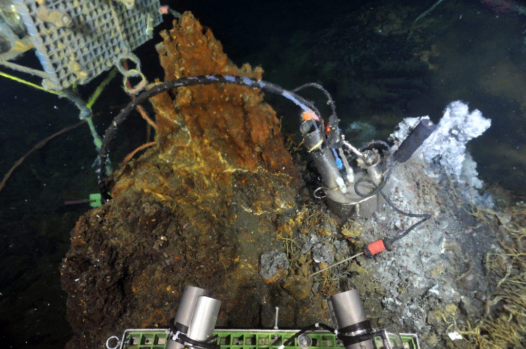 A titanium 'cap' is placed on the top of El Gordo by ROPOS, which focuses the diffuse fluid so that a fluid and microbial DNA sampler can get hydrothermal fluids samples largely undiluted by seawater. The fluid-DNA sampler is in the background. Credit: NSF-OOI/UW/ISS; Dive R1836; V15.