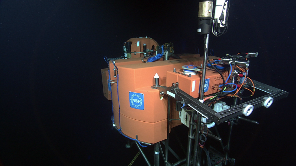 A side view of the 12 foot-acoss Shallow Profiler platform on a 2700 m-tall, 2 legged mooring with an instrument package in the foreground hosting acoustic doppler current profilers, a digital still camera, and a variety of chemical and biological sensors. The 'head' of the shallow winched profiler science pod rises above the platform in the background. Credit: NSF-OOI/UW/ISS; Dive R1834; V15.
