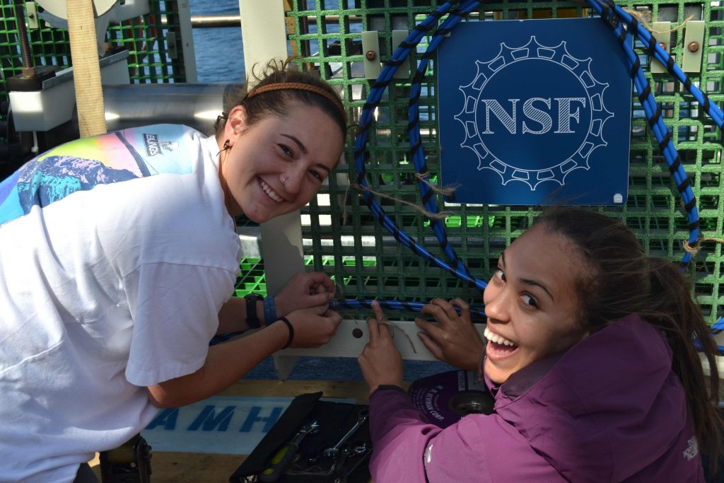 Jessie and Kadijah help prepare an instrument cable on a junction box, which provides power and communication to a variety of chemical and biological sensors that will provide live streaming data to shore from 2900 m water depth (over 10,000 ft beneath the ocean's waves). Credit: Lauren Kowalski, University of Washington.