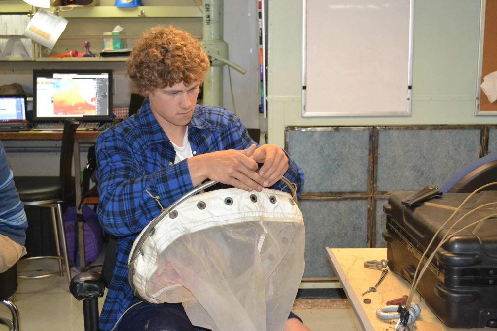 Jesse Turner, UW School of Oceanography senior, prepares a zoonplankton net to sample organisms in the deep sea as part of the VISIONS15 program. Credit: Mitch Elend, University of Washington